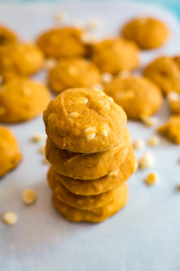 A stack of White Chocolate Macadamia Nut Pumpkin Cookies taken frm a high angle with other cookies in the background.