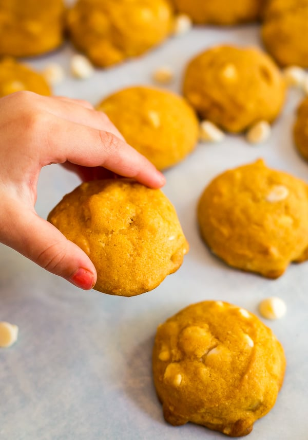 A child's hand holding a White Chocolate Macadamia Nut Pumpkin Cookie.