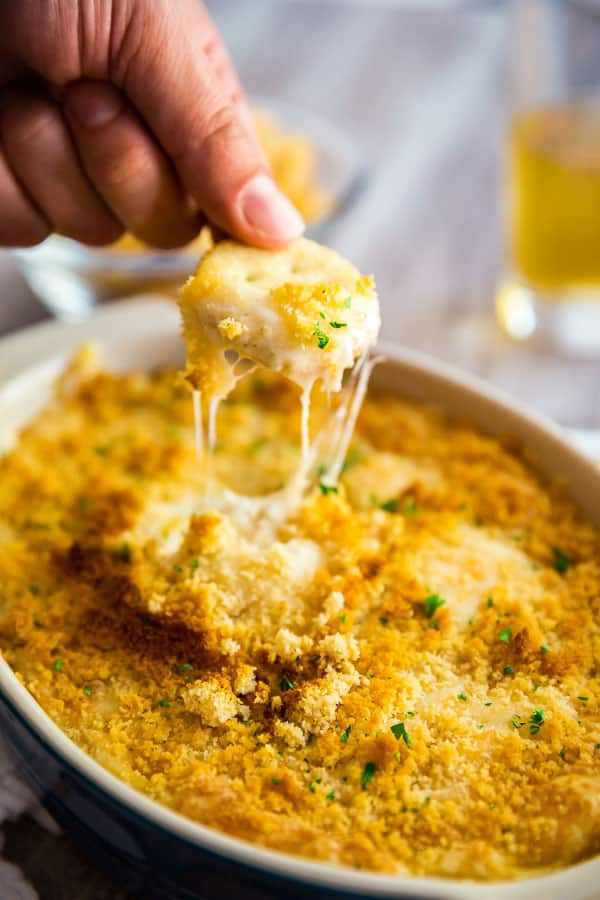 A hand pulling up a cracker full of Hot Chicken Swiss Dip from a pan of the dip with stringy cheese trailing.