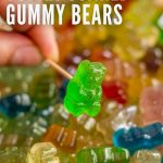 A hand holding a toothpick with a boozy gummy bear on it with a bunch of the gummy bears behind it.