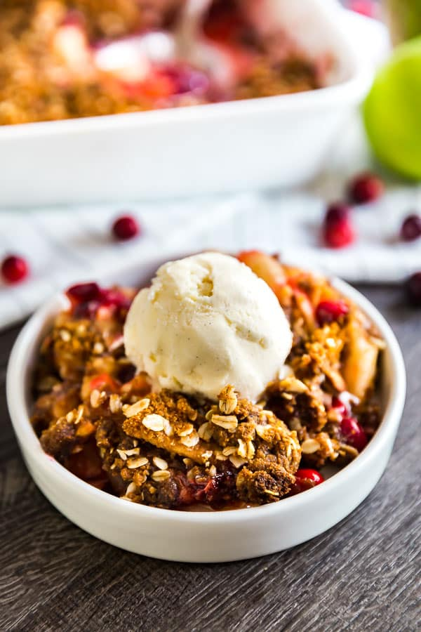 A round white plate with Cranberry Apple Crisp Recipe with Oatmeal Ginger Snap Topping topped with vanilla ice cream and a pan of it in the background.