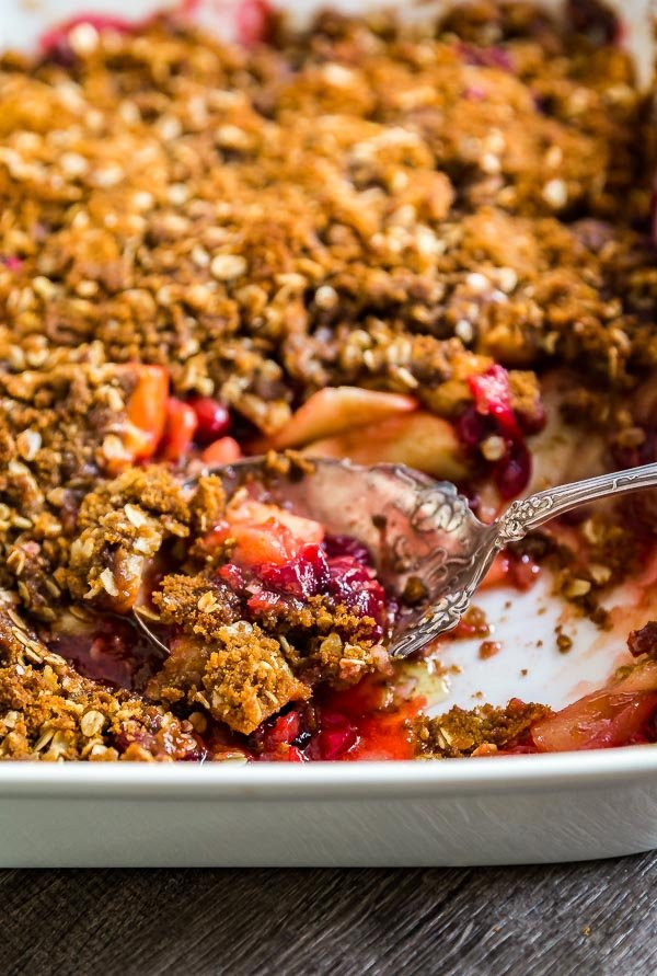 A pan of Cranberry Apple Crisp Recipe with Oatmeal Ginger Snap Topping with some of it missin and the serving spoon in the pan.