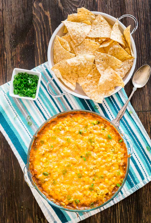 An overhead image of Hot 7 Layer Bean Dip with chips and green onions on the side.
