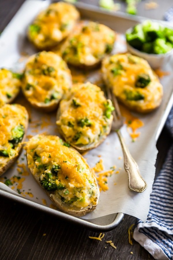 Cheddar and Broccoli Twice Baked Potatoes on a pan lined with parchment paper.
