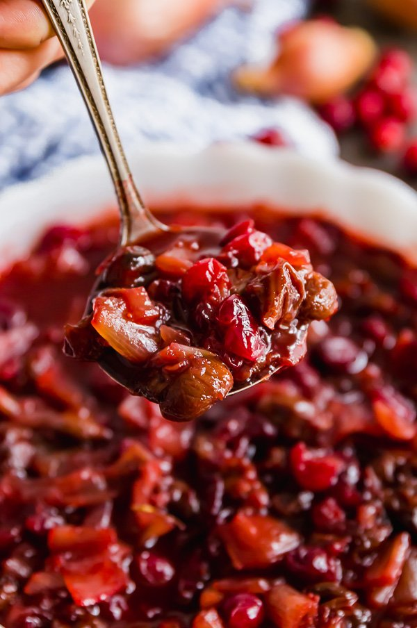 A close up of a ladle full of Homemade Cranberry Sauce with Dried Cherries and Shallots.