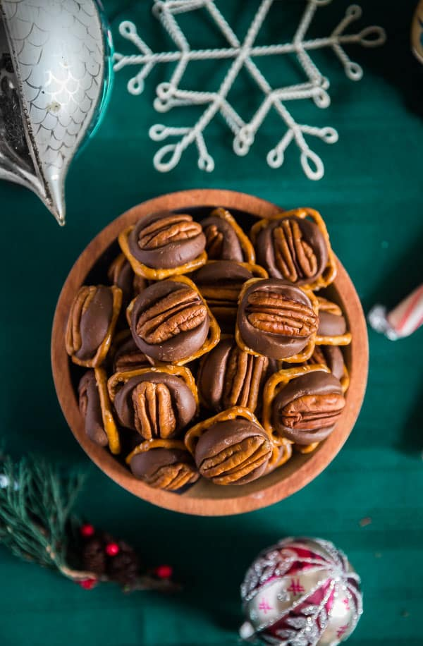 An overhead image of a bowl of Chocolate Caramel Pretzel Turtles on a green table cloeth with christmas accessories around it.
