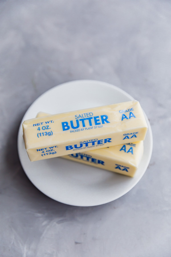 An overhead shot of two sticks of butter on a plate from how to soften butter