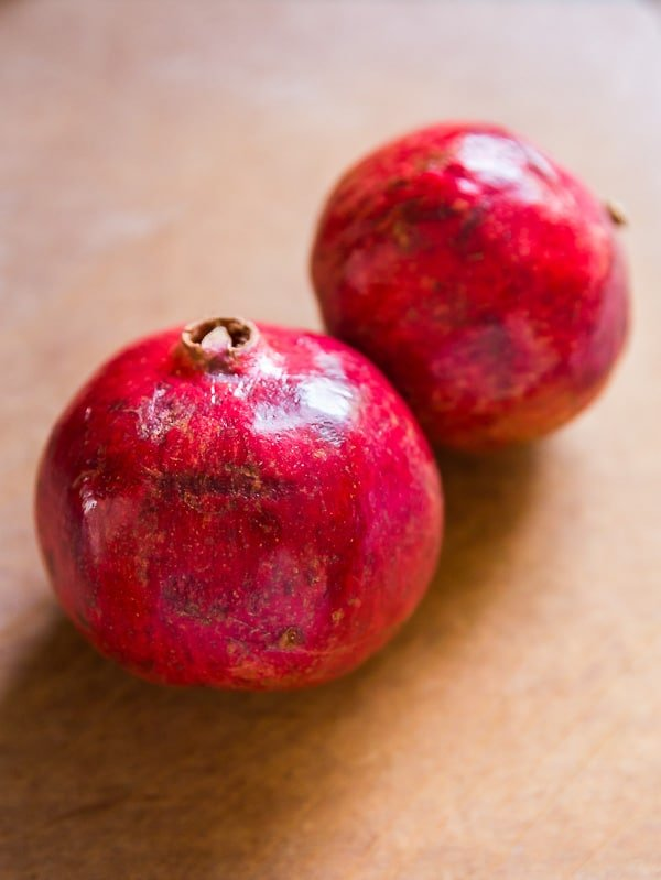 Two whole pomegranates on a cutting board for How to peel a pomegranate.
