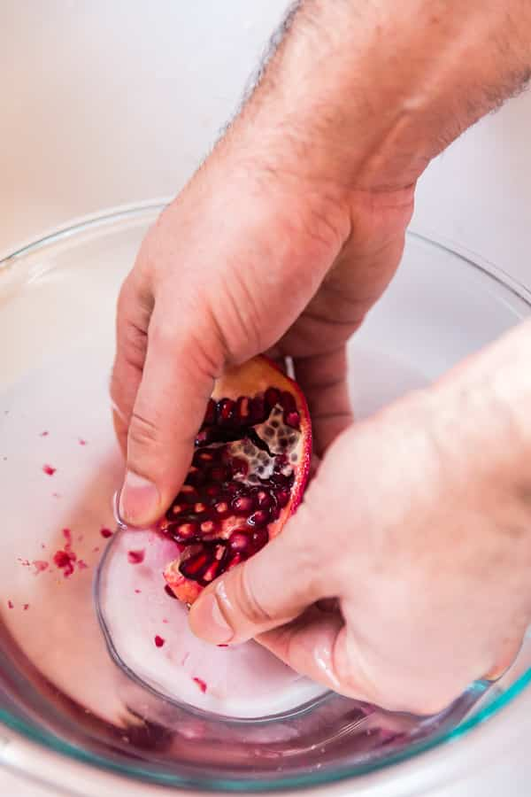 Hands peeling a pomegranate in a bowl of water for How to peel a pomegranate