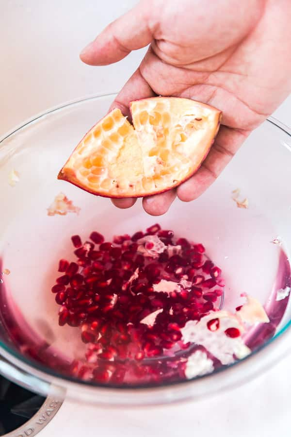 A hand holing an empty pomegrante peel for How to peel a pomegranate.