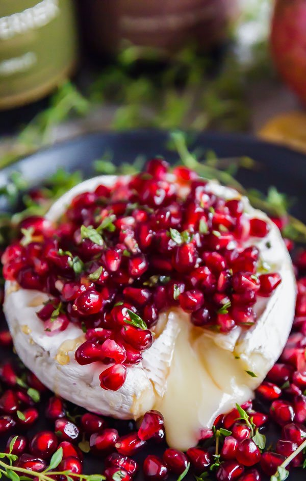 A close up image of Pomegranate and Thyme Baked Brie Appetizer with brie flowing out of it.