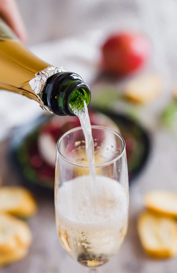 Sparkling wine pouring into a glass with Pomegranate and Thyme Baked Brie Appetizer in the background.