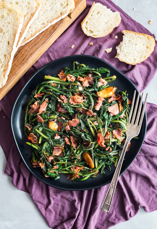 An overhead image of Spicy Dandelion Greens on a black plate with bread on the side.
