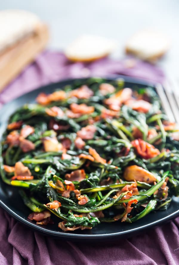 Spicy Dandelion Greens on a black plate with pieces of bread in the background.