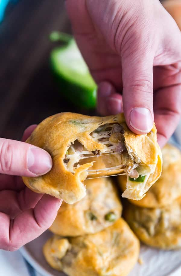 A hand pulling apart a Philly Cheese Steak Stuffed Bread Roll with stretchy cheese.