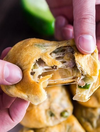 A square image of a hand pulling apart a Philly Cheese Steak Stuffed Bread Roll.