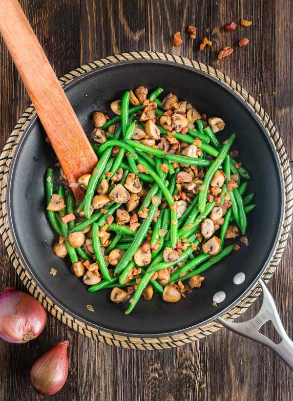 An overhead image of Sauteed Green Beans with Mushrooms, Shallots and Pancetta in a pan.