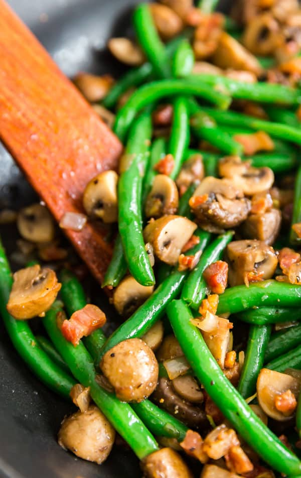 A close up shot of Sauteed Green Beans with Mushrooms, Shallots and Pancetta in a pan.