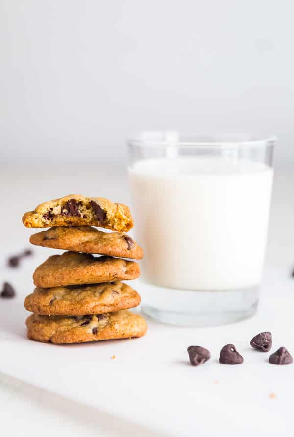 A stack of cookies from the Toll House Cookie Recipe next to a glass of milk.