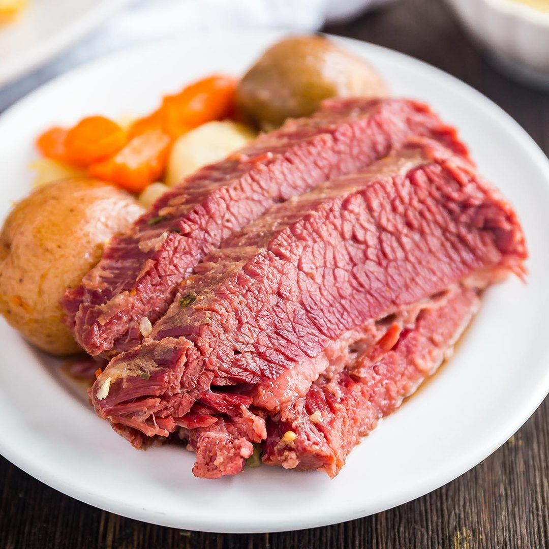 A square image of slices of corned beef on a white plate with potatoes and carrots in the background on the plate.