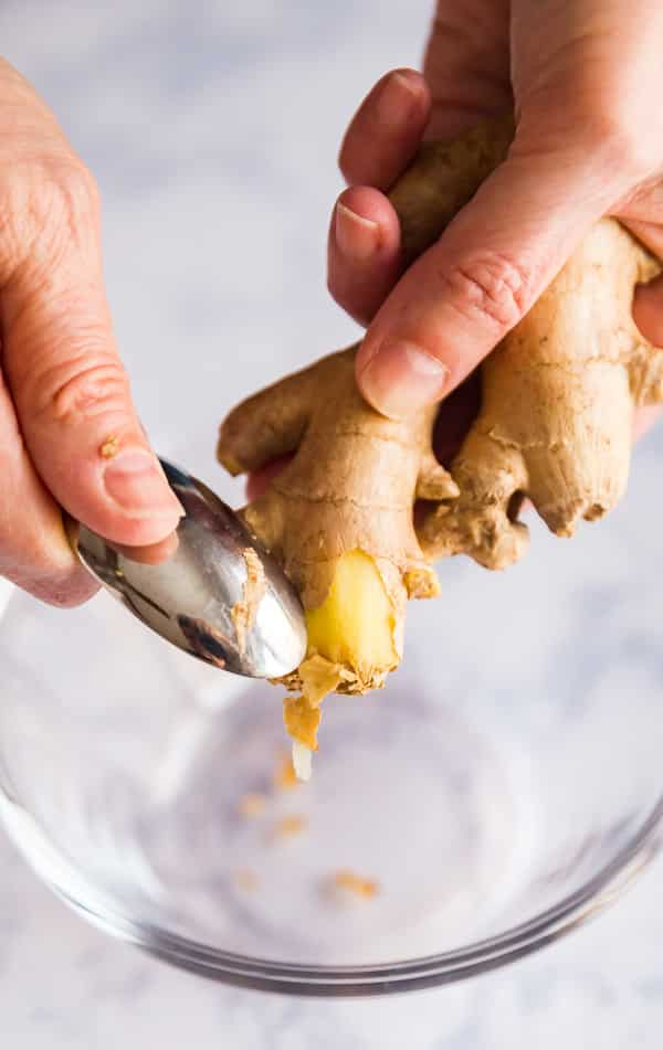 Hands using a spoon to peel ginger.