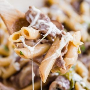 A square image of a wooden spoon holding a scoop of philly steak pasta with the rest of the pan behind it.