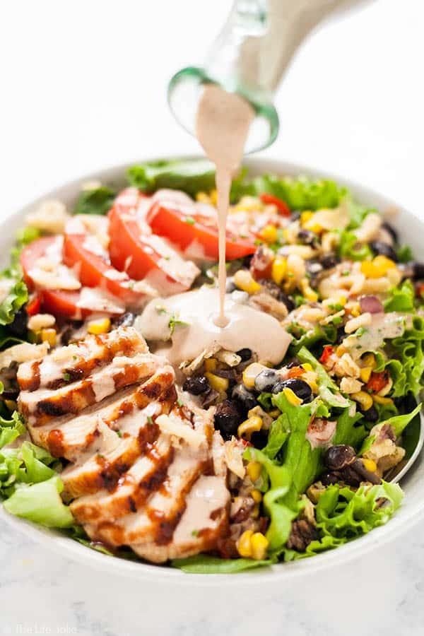 A close up image of bbq ranch dressing bring poured on a green salad with chicken, corn, black beans and tomatoes in a white bowl.