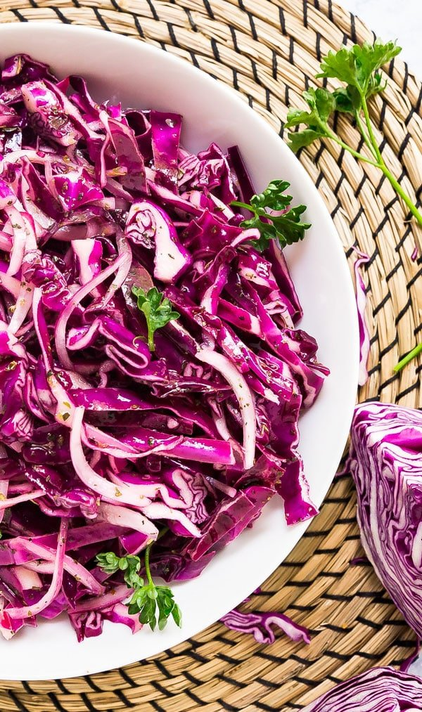 An overhead image zooming in on half a white bowl of red cabbage slaw.