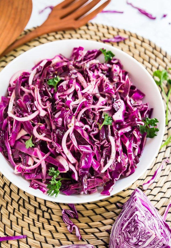 A bowl of purple cabbage salad on a woven mat with wooden salad tongs behind it.