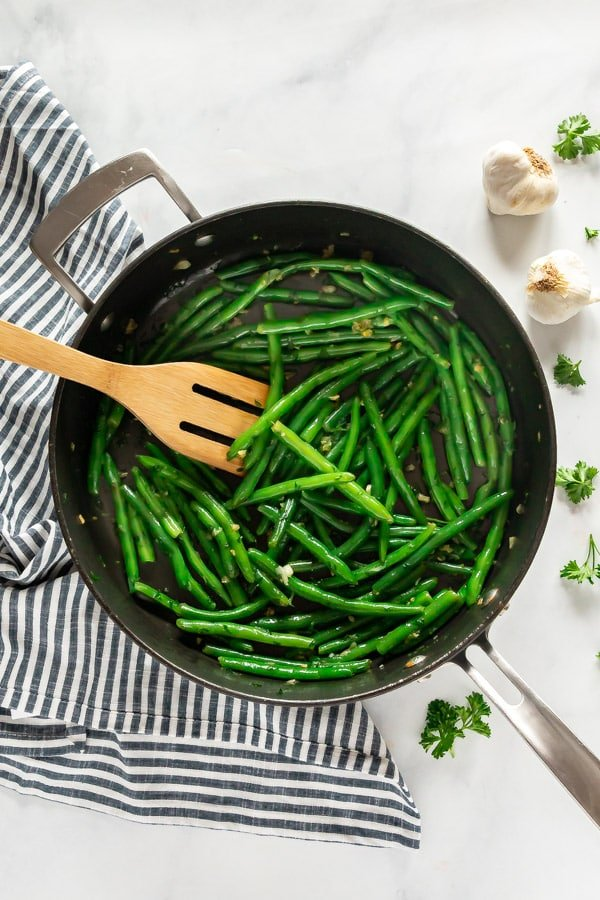 An overhead image of green beans in a saute pan.