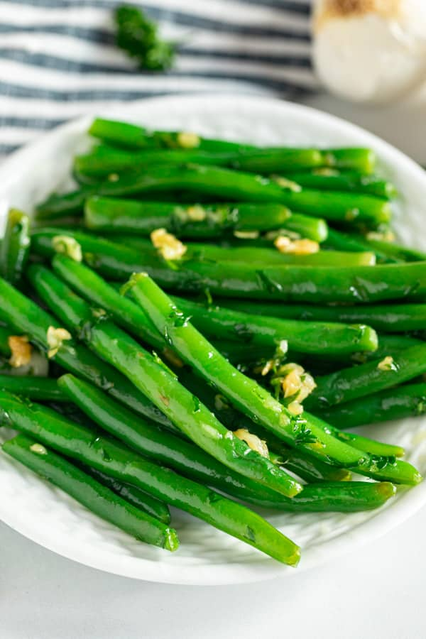A close up shot of garlic green beans on a plate