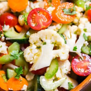 A square close up overhead image zooming in on the veggies in the marinated vegetables salad including cauliflower, cherry tomatoes, carrots, celery, cucumbers and onion.