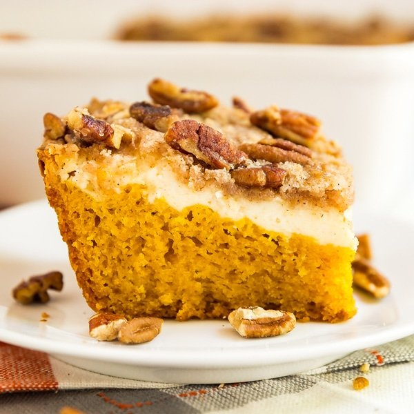 Cream Cheese Pumpkin Crunch Cake is the seriously easy fall dessert that you'll want to bring to every party! This cake mix hack includes a pumpkin sheet cake, cheesecake layer and a crumbly streusel topping with pecans. Every single person who tries it goes crazy over it and begs for the recipe.