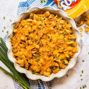 A square overhead image of Frito Pie in a pan with scallions around it and a bag of Fritos on the side spilling out.