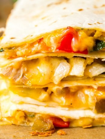 A square close up image of the edge of a stack of quesadilla on top of each other showcasing the gooey cheese and fillings.