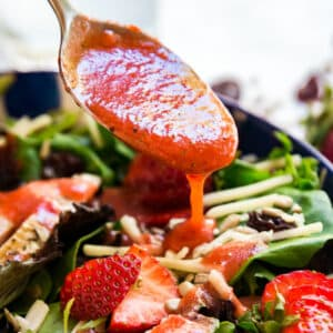 Summer Bounty Strawberry Salad with Fresh Strawberry Vinaigrette is a light and fresh lunch! Made with some unexpected ingredients like greens, strawberries, white cheddar, sunflower seeds and dried cherries this salad is as healthy as it is delicious!