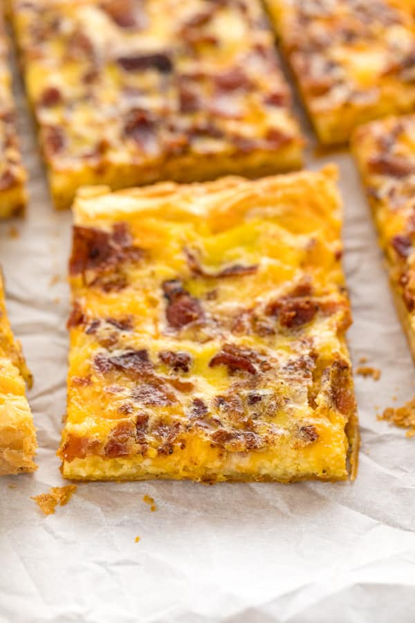 Puff pastry breakfast pizza slice on a piece of parchment paper with other slices around it.