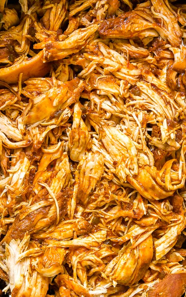 A close up overhead image of bbq pulled chicken crock pot style.
