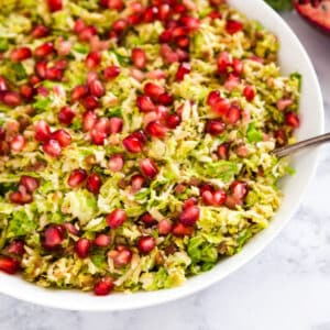 These Sautéed Shredded Brussel Sprouts and a festive holiday side dish recipe that's also super quick and easy to make! Made with Brussel Sprouts, Shallots, Pancetta, Holland House Sherry Cooking Wine and fresh Pomegranate Seeds.