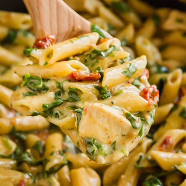 A square image of a wooden spoon holding a scoop of florentine pasta with chicken with the rest of the pasta in the pan in the background.