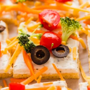 A square close up image of a piece veggie pizza surrounded by other pieces.
