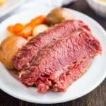 An image of slices of corned beef on a white plate with potatoes and carrots in the background on the plate.