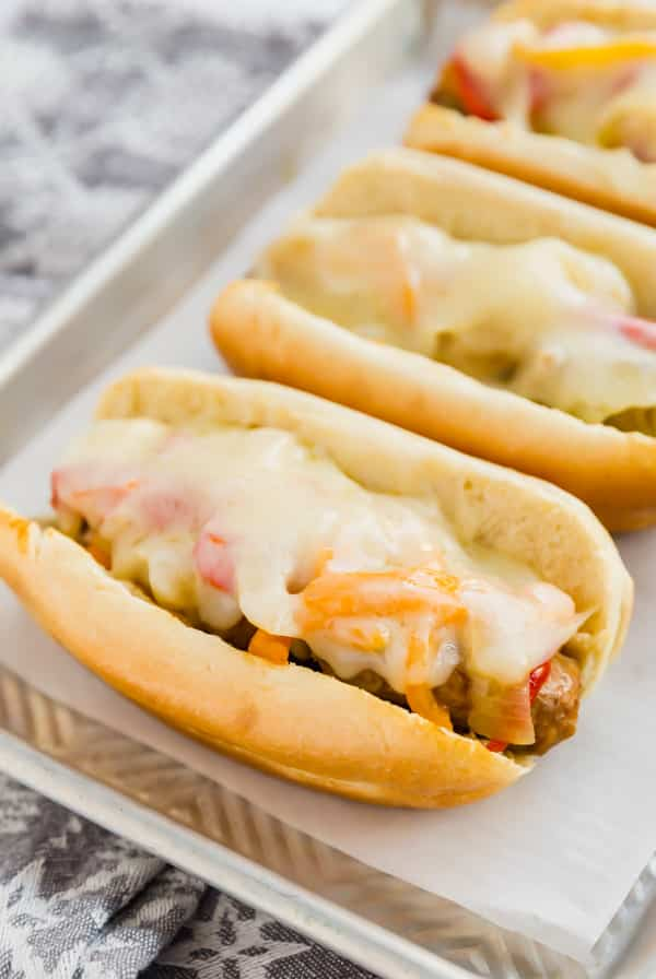 Buns with sausage and peppers and melted cheese on top on white rectangular plate.