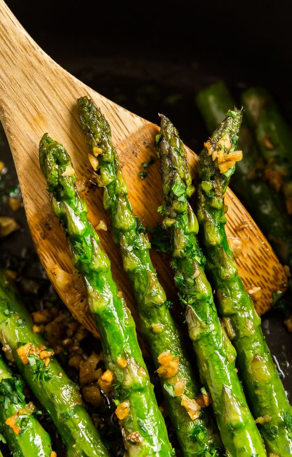A wooden spoon holding up spears of this asparagus recipe
