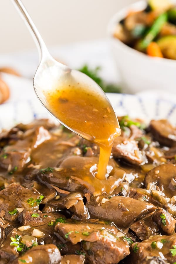 A spoon pouring gravy over this steak tips recipe