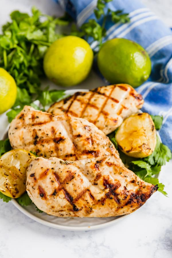 An image of a plate of cilantro lime chicken with limes and cilantro around it.