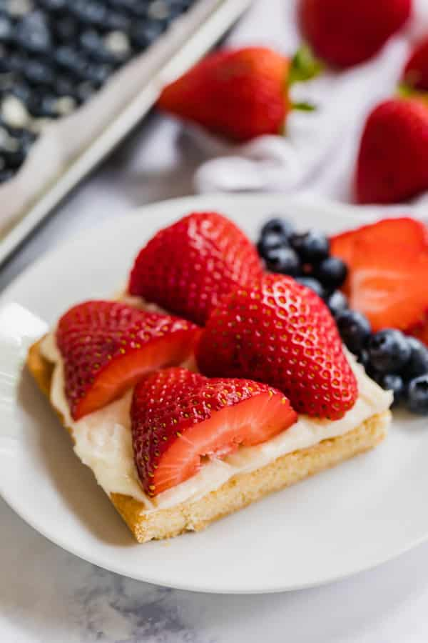 A slice of sugar cookie fruit pizza on a plate.
