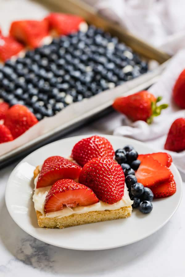 A side angle photo of a slice of this fruit pizza recipe with the rest of it in the background.