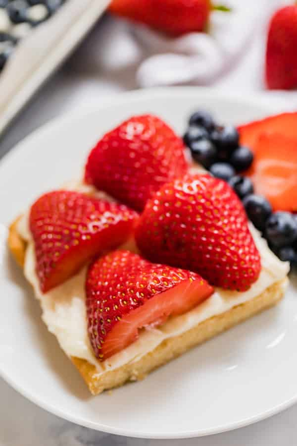 A close up photo of a slice of fruit pizza.