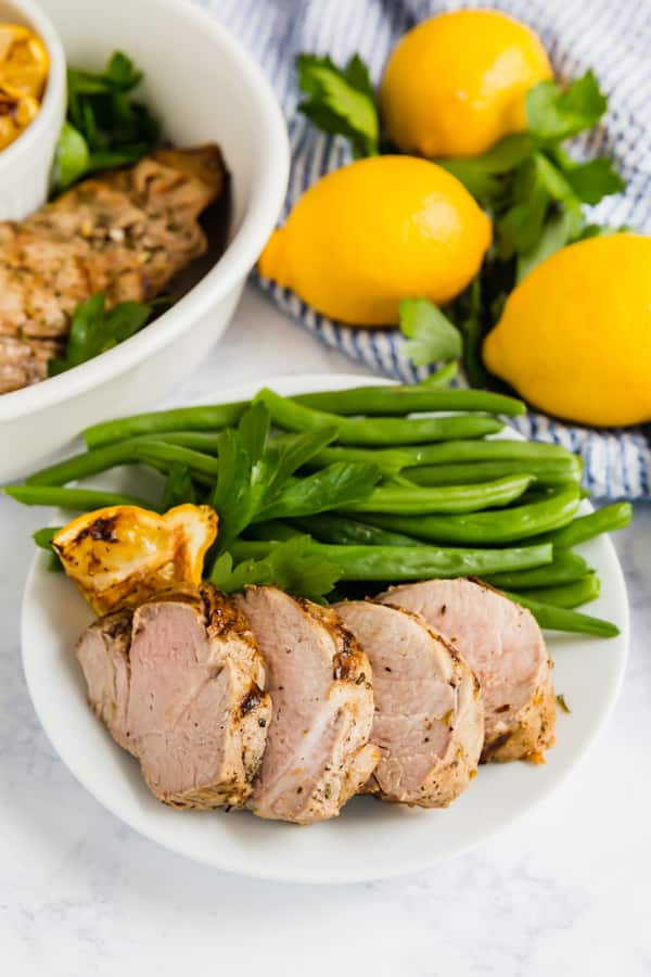 Greek pork tenderloin on a plate with green beans